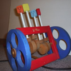 "Just a wood toy to entertain a child. You can see the off center cams that pump the ""heads"" up and down and their wheel base is off center s"