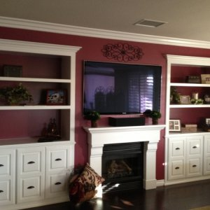 Two built in bookshelves with crown molding on top and crown molding across the room.