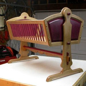 baby cradle features knock down design for easy storage. Quarter sawn white oak and purpleheart.