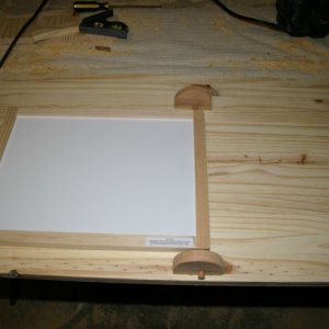 "blocks inset 1/8"" into lid.  3/8"" dowel inserted through block and into edge of board on either side."